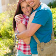 Stock Photo: Young happy couple embracing in sunny park