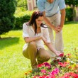 Young couple look flowers in sunny park - Stock Photo