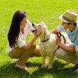 Foto Stock: Young happy couple playing with Labrador dog