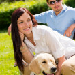 图库照片: Couple sitting with golden retriever in park