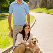 Happy couple with dog on park alley — Stock Photo