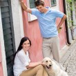 Happy couple resting with dog on street — Stock Photo