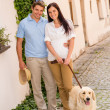 Modern couple with dog in romantic city — Stock Photo