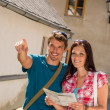 Young couple in city man pointing direction — Stock Photo