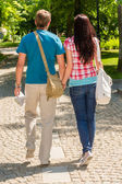 Couple holding hands walking in the park — Stock Photo