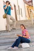 žena čte knihy o schody člověka fotografování — Stock fotografie