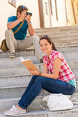 Woman sitting on stairs reading man photographing — Stock Photo