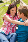 Young happy couple hugging in park sitting — ストック写真