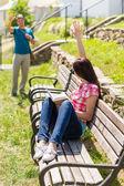 Woman waving to man sitting on bench — ストック写真