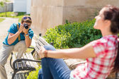 Man taking pictures of woman on bench — Stock Photo