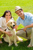 Young happy couple with Labrador dog — Stockfoto