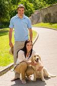 Gelukkige paar met de hond op park alley — Stockfoto