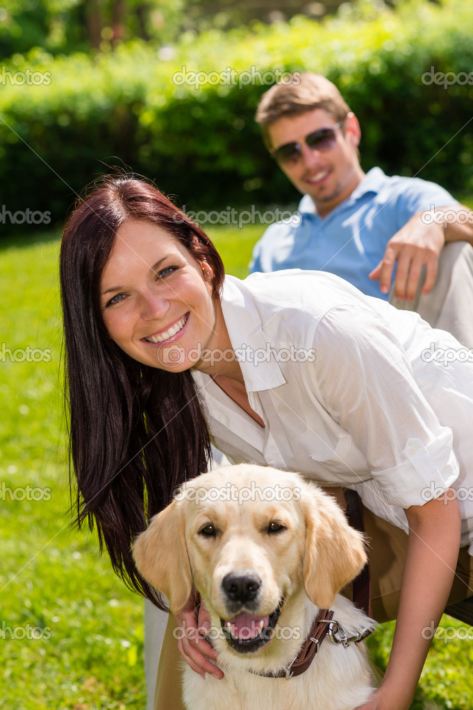 Happy young couple sitting with golden retriever dog in park — Stock Photo #12447681