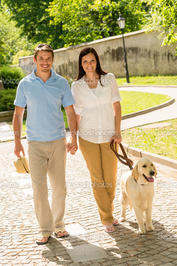 Couple in love walking Labrador dog in park sunny day  Stock Photo #12447697