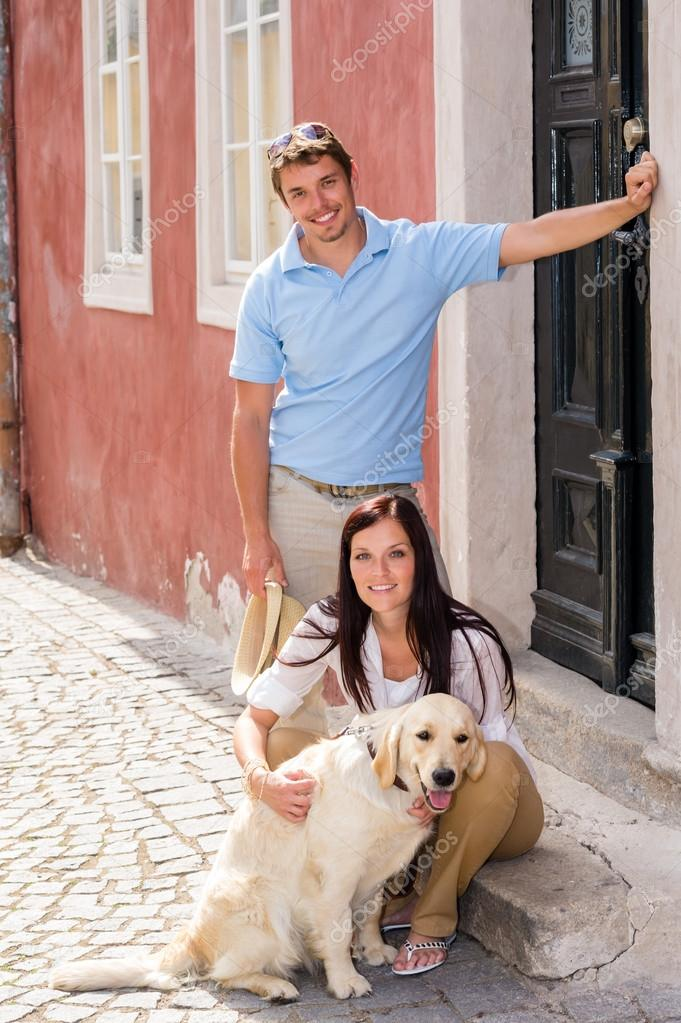 Young couple resting with dog on street stairs happy pet — Stock Photo #12447713
