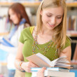 Teenage student with book at high school library — Stock Photo
