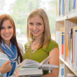 Girl friends studying books together in library — Stock Photo