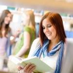Teenage woman read among book shelves library — Stock Photo #12588785