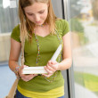 Student girl reading book standing by window — Stock Photo