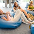 Group of students relax on beanbag — Stock Photo