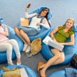 Group of students relax on beanbag - Stock Photo