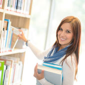 Happy student choosing books from library shelf — Stock Photo