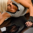 Woman kickboxer in black relax on floor — Stockfoto