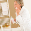 Mature woman bathroom clean face make-up removal — Stock Photo