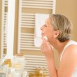 Senior woman clean face with cotton pad — Stock Photo