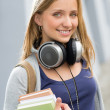 Teenage girl outdoor holding books with headphones — Stock Photo