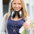Young teenage student girl with books headphones — Stock Photo