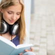Stock Photo: Student reading a book outside of university