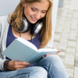 Smiling young student reading book outside school - Foto Stock