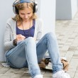 Student teenager writing and listening to music — Stock Photo