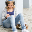 Royalty-Free Stock Photo: Student teenager writing and listening to music