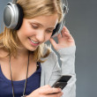 Young woman with headphones checking mobile phone — Stock Photo