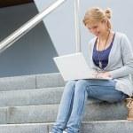 女学生在楼梯上带着笑容的笔记本电脑 — 图库照片