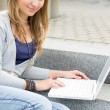 Foto Stock: Teenage girl study with laptop sitting stairs