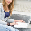 Stock Photo: Teenage girl study with laptop sitting stairs
