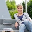 Young student sitting on university steps laptop — Stok fotoğraf