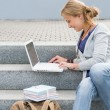 Student woman sitting on steps work laptop - Stok fotoğraf