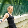Sportive girl resting against fence after workout — Stock Photo