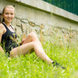 Stock Photo: Young sportive womrelax in grass workout