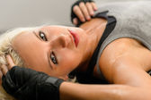 Woman kickboxer in black relax on floor — Stock Photo