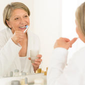 Senior woman brushing teeth bathroom mirror reflection — Stock Photo