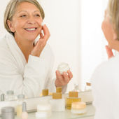Senior woman apply anti-wrinkles cream look mirror — Stock Photo