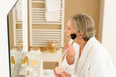 Senior woman apply make-up powder in bathroom — Stock Photo
