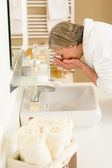 Senior woman wash face at basin bathroom — Stock Photo