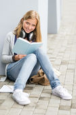 Student reading book outside of school young — Stock Photo