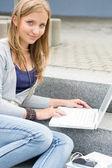 Studio di adolescente con portatile seduti scale — Foto Stock